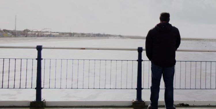 childhood sex abuse victim standing on a beach